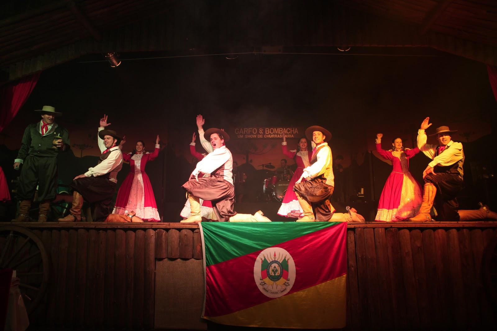 Foto que mostra vários dançarinos gaúchos, dançando a famosa chula. Destaque para a bandeira do Rio Grande do Sul.