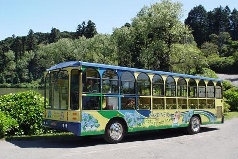 Foto que mostra o ônibus da Jardineira das Hortênsias estacionado próximo ao famoso Lago Negro, em Gramado.