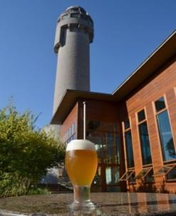 Imagem mostra uma cervejaria na Serra, com destaque à torre da cervejaria e a um copo de cerveja