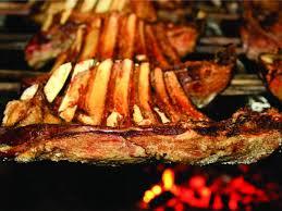 Foto que mostra carne de costela em uma churrasqueira