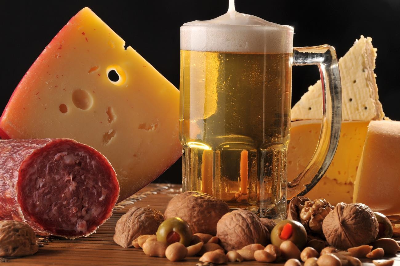A foto mostra um pedaço de queijo e linguiça, além de uma caneca de Choop